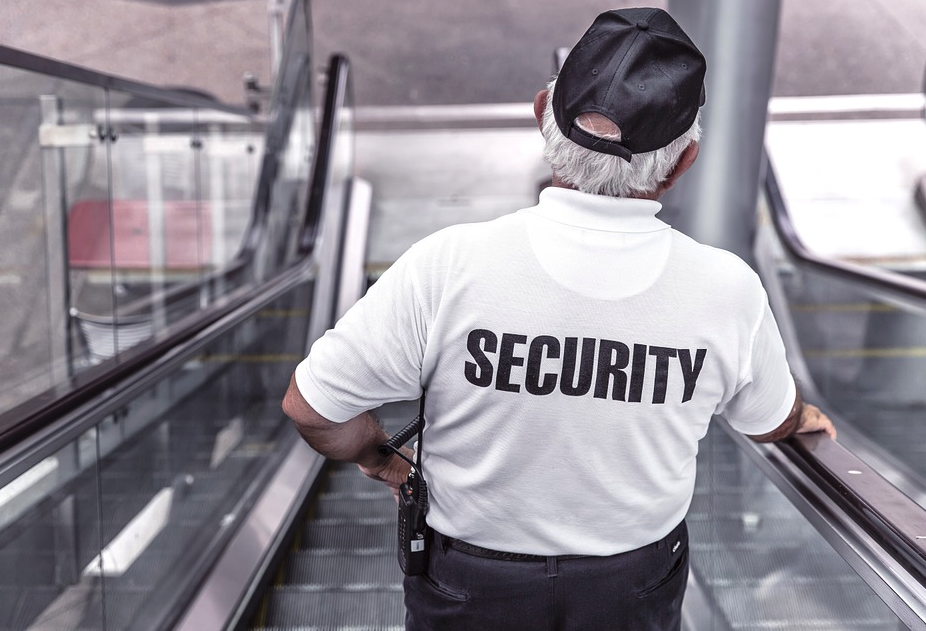 An older man with a security shirt and cap is on the escalators of a shopping center looking at the patrons.